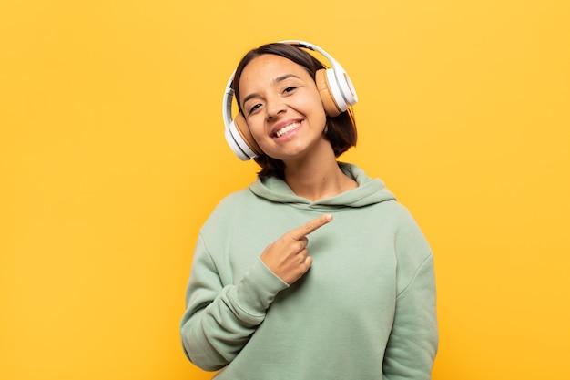 Junge lateinische frau, die fröhlich lächelt, sich glücklich fühlt und zur seite und nach oben zeigt und das objekt im kopierraum zeigt