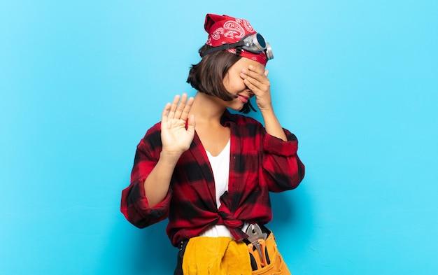 Junge lateinische frau, die gesicht mit der hand bedeckt und fotos ablehnt