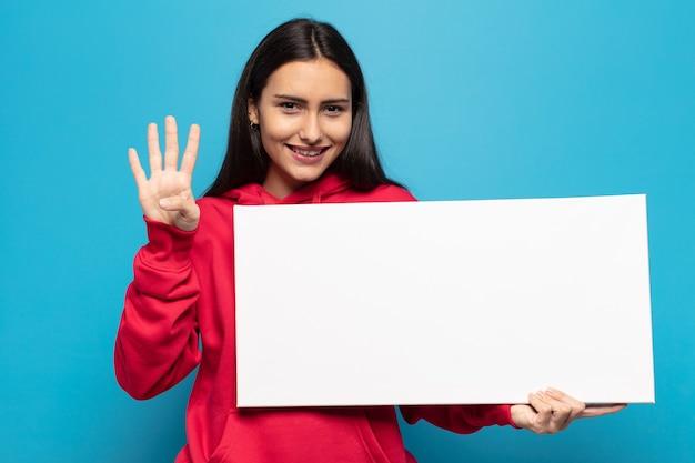 Junge lateinische frau, die lächelt und freundlich schaut, nummer vier oder vierten mit der hand vorwärts zeigend, herunterzählend