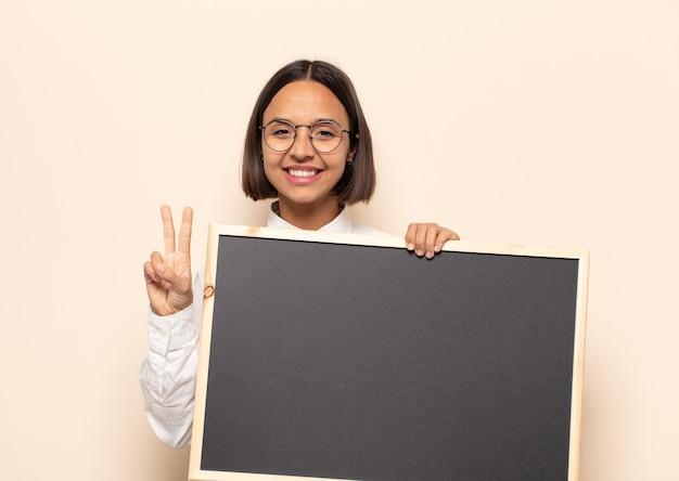 Junge lateinische frau, die lächelt und freundlich schaut, nummer zwei oder sekunde mit der hand vorwärts zeigend, herunterzählend