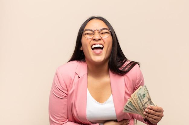 Junge lateinische frau, die laut über einen urkomischen witz lacht, sich glücklich und fröhlich fühlt und spaß hat