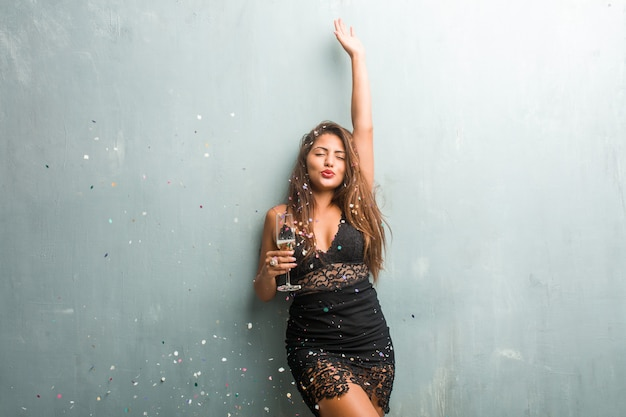 Junge lateinische frau, die neues jahr oder ein ereignis feiert. aufgeregt und glücklich, hält eine champagnerflasche und eine tasse.