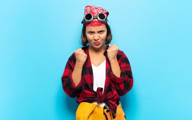 Junge lateinische frau, die selbstbewusst, wütend, stark und aggressiv aussieht, mit fäusten, die bereit sind, in boxposition zu kämpfen