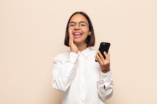 Junge lateinische frau, die sich glücklich, aufgeregt und positiv fühlt, mit den händen neben dem mund einen großen schrei ausstößt und schreit
