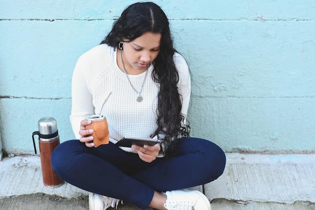 Junge lateinische frau, die traditionellen yerba-kameradentee mit tablette trinkt