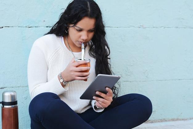 Junge lateinische frau, die traditionellen yerba kameradtee mit tablette trinkt