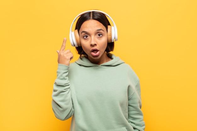 Junge lateinische frau, die überrascht, mit offenem mund, schockiert aussieht und einen neuen gedanken, eine neue idee oder ein neues konzept realisiert