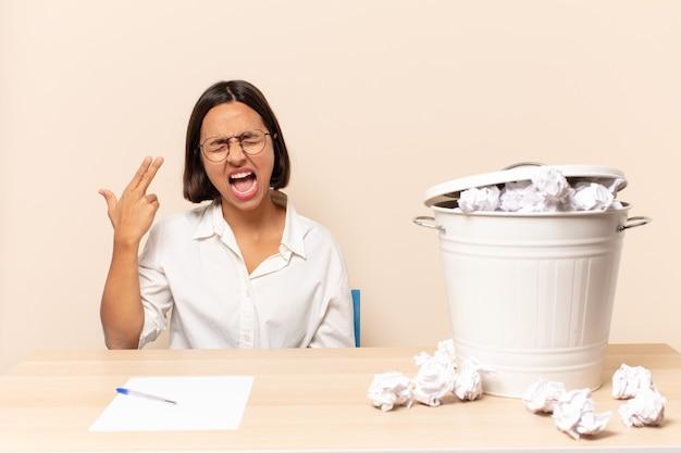 Junge lateinische frau, die unglücklich und gestresst aussieht, selbstmordgeste, die waffenzeichen mit der hand macht und auf den kopf zeigt