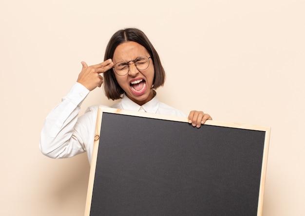 Junge lateinische frau, die unglücklich und gestresst schaut, selbstmordgeste, die waffenzeichen mit hand macht, zeigt auf kopf