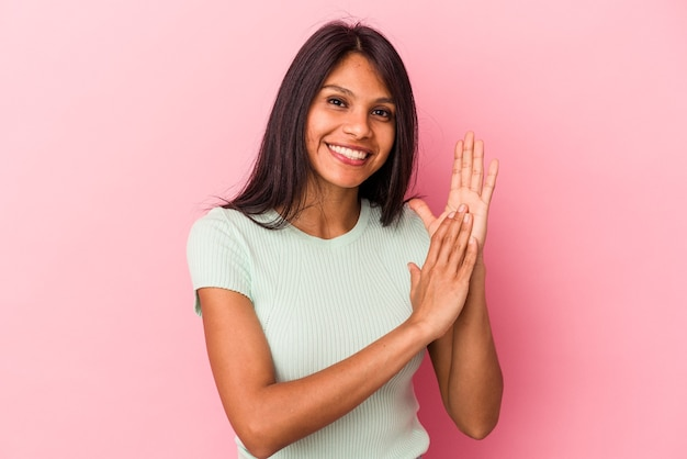 Junge lateinische frau einzeln auf rosafarbenem hintergrund, die sich energisch und bequem fühlt und sich die hände selbstbewusst reibt.