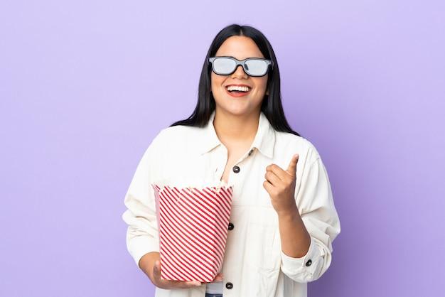 Junge lateinische frau frau auf weißer wand mit 3d-brille und hält einen großen eimer popcorn, während sie nach vorne zeigt