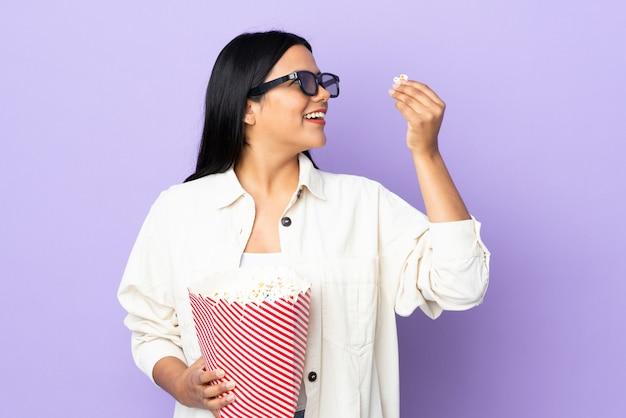 Junge lateinische frau frau auf weißer wand mit 3d brille und hält einen großen eimer popcorn