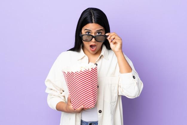 Junge lateinische frau frau auf weißer wand überrascht mit 3d-brille und hält einen großen eimer popcorn