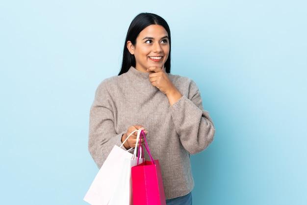 Junge lateinische frau frau lokalisiert auf blauer wand, die einkaufstaschen hält und denkt