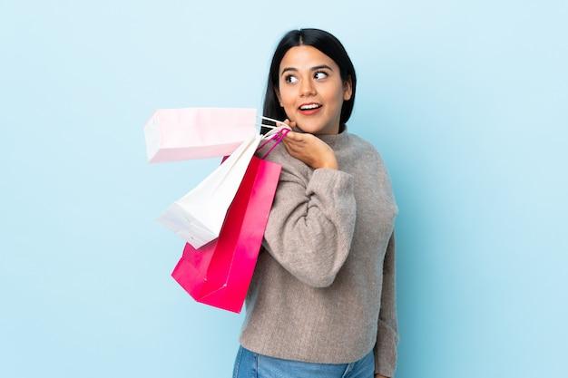 Junge lateinische frau frau lokalisiert auf blauer wand, die einkaufstaschen hält und lächelt