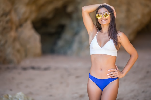 Junge lateinische frau im bikini, der nahe felsen schaut, die während der sommerferien auf meer schauen
