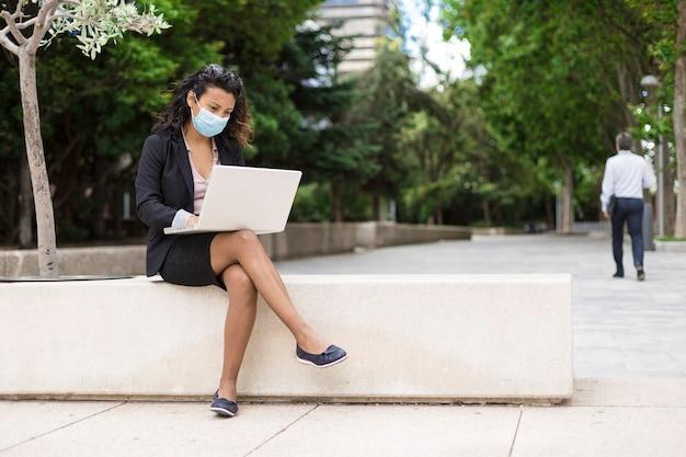 Junge lateinische frau in der formellen kleidung, die an laptop arbeitet. sie ist draußen und trägt eine gesichtsmaske.