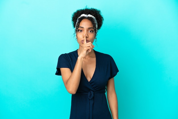 Junge lateinische frau isoliert auf blauem hintergrund, die ein zeichen der stille zeigt, geste, die den finger in den mund steckt