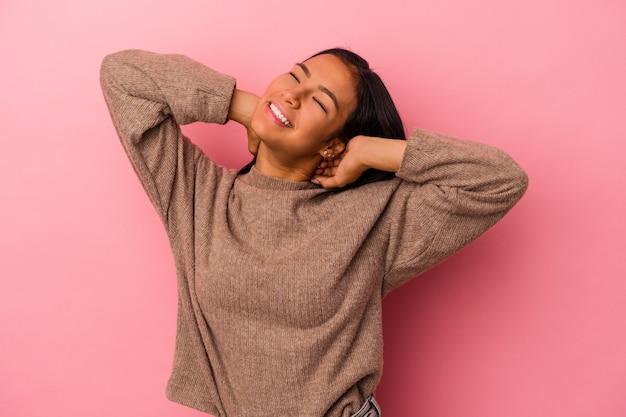 Junge lateinische frau isoliert auf rosa hintergrund, die arme ausdehnt, entspannte position.