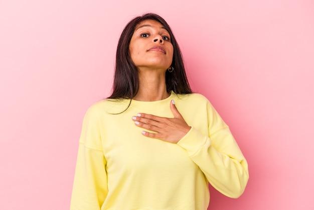 Junge lateinische frau isoliert auf rosa hintergrund, die einen eid leistet und die hand auf die brust legt.