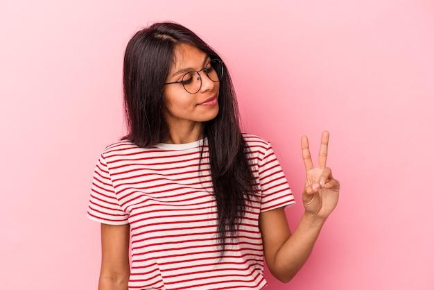 Junge lateinische frau isoliert auf rosa hintergrund fröhlich und sorglos, die ein friedenssymbol mit den fingern zeigt.