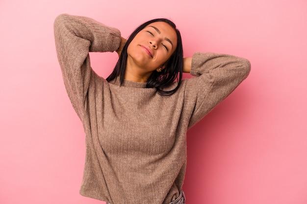 Junge lateinische frau isoliert auf rosa hintergrund selbstbewusst, mit den händen hinter dem kopf.