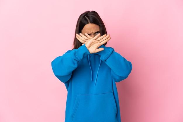 Junge lateinische frau isoliert auf rosa wand, die stoppgeste mit ihrer hand macht, um eine handlung zu stoppen