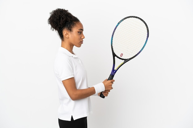 Junge lateinische frau isoliert auf weißem hintergrund beim tennisspielen