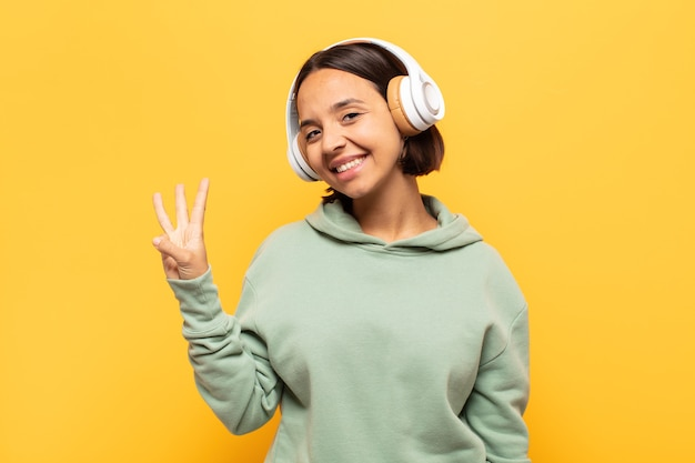 Junge lateinische frau lächelt und sieht freundlich aus, zeigt nummer drei oder dritte mit der hand nach vorne und zählt herunter