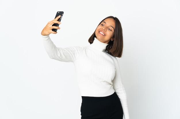 Junge lateinische frau lokalisiert auf weißem hintergrund, der ein selfie macht