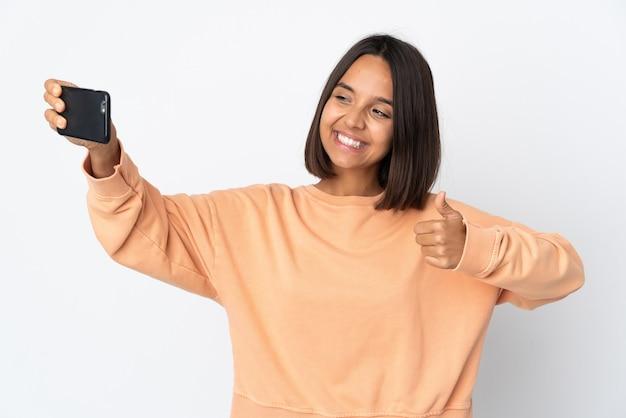 Junge lateinische frau lokalisiert auf weißem hintergrund, der ein selfie mit handy macht