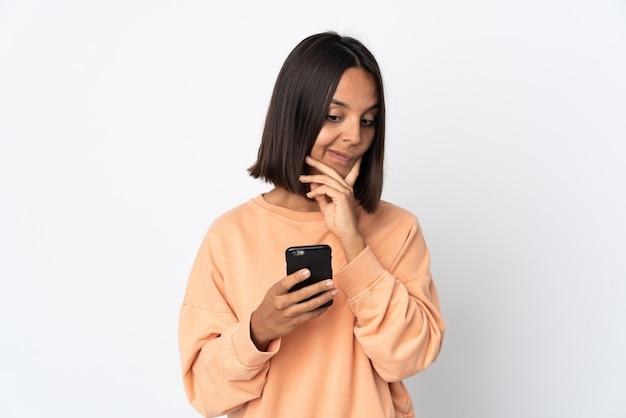 Junge lateinische frau lokalisiert auf weißem hintergrund unter verwendung des mobiltelefons und des denkens