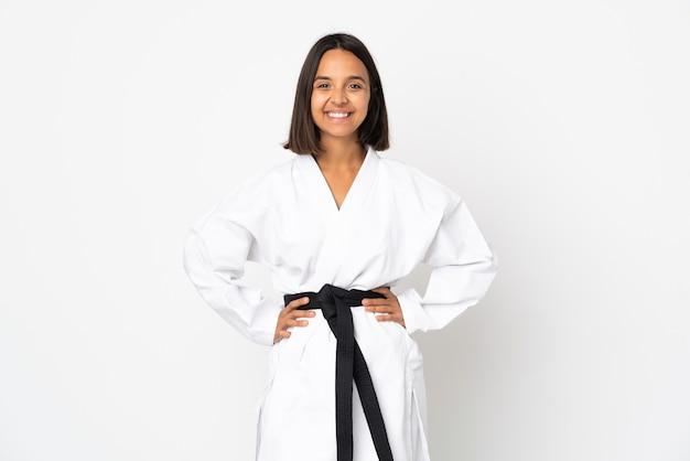 Junge lateinische frau lokalisiert auf weißer wand, die karate tut, das mit armen an der hüfte aufwirft und lächelt