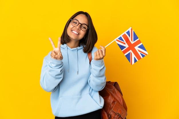 Junge lateinische frau mit einer flagge des vereinigten königreichs isoliert auf gelbem hintergrund lächelt und zeigt victory-zeichen
