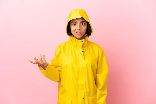Junge lateinische frau trägt einen regendichten mantel über isoliertem hintergrund und macht zweifel geste