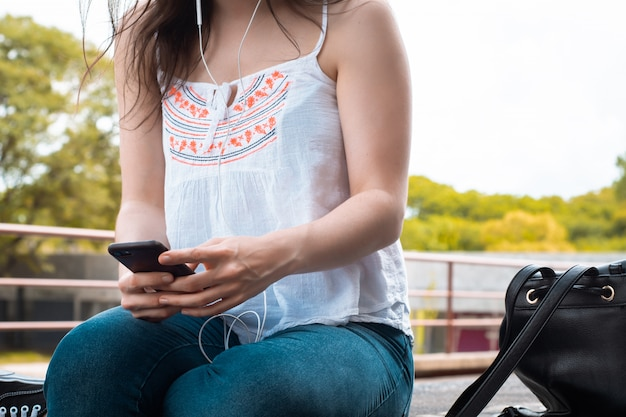 Junge lateinische frauen, die mitteilung mit smartphone senden.