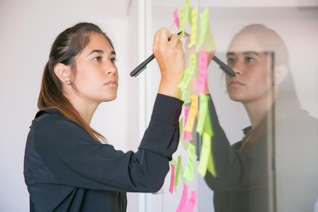 Junge lateinische geschäftsfrau, die auf aufkleber mit markierung schreibt. fokussierte selbstbewusste schöne brünette managerin, die idee für projekt teilt und notiz macht. brainstorming-, geschäfts- und schulungskonzept