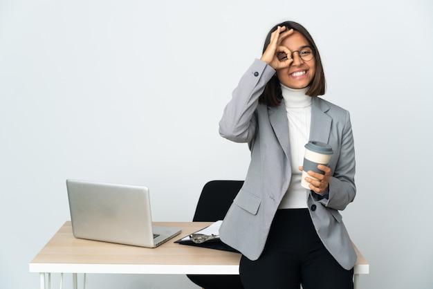 Junge lateinische geschäftsfrau, die in einem büro arbeitet, das auf weißem hintergrund lokalisiert wird, das okayzeichen mit den fingern zeigt