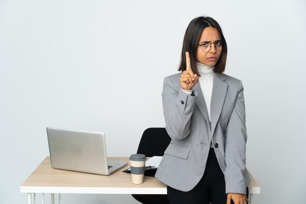 Junge lateinische geschäftsfrau, die in einem büro arbeitet, das auf weißem hintergrund lokalisiert wird, der einen mit ernstem ausdruck zählt