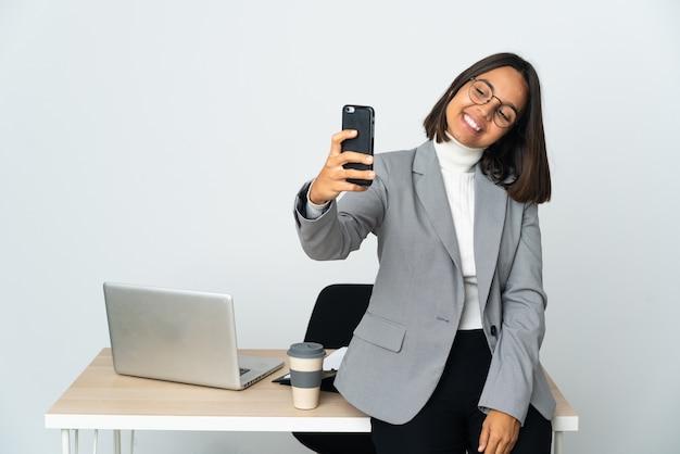 Junge lateinische geschäftsfrau, die in einem büro arbeitet, das auf weißer wand lokalisiert wird, die ein selfie macht