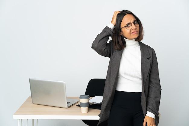 Junge lateinische geschäftsfrau, die in einem büro arbeitet, das auf weißer wand mit einem ausdruck der frustration und des nichtverständnisses isoliert wird