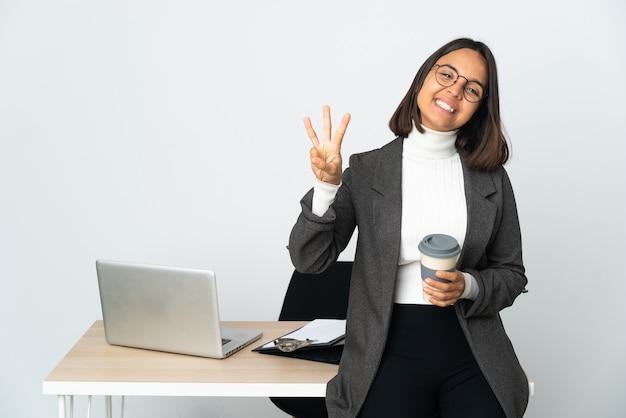 Junge lateinische geschäftsfrau, die in einem büro arbeitet, lokalisiert auf weißem hintergrund glücklich und drei mit den fingern zählend