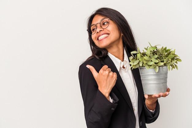 Junge lateinische geschäftsfrau, die pflanzen lokalisiert auf weißem hintergrund hält, zeigt mit dem daumenfinger weg, lacht und sorglos.