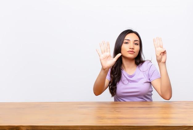 Junge lateinische hübsche frau, die lächelt und freundlich schaut, nummer acht oder acht mit der hand nach vorne zeigend, gegen flache wand herunterzählend