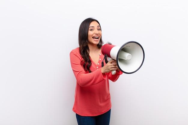 Junge lateinische hübsche frau gegen flache wand mit einem megaphon