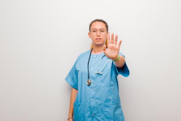 Junge lateinische krankenschwester, die ernst, streng, unzufrieden und wütend aussieht und offene handfläche zeigt, die stoppgeste über weiße wand macht