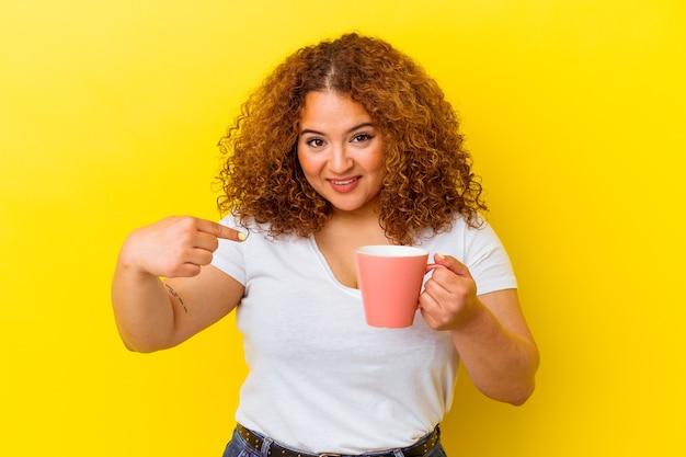 Junge lateinische kurvige frau, die eine tasse lokalisiert auf gelbe hintergrundperson hält, die von hand auf einen hemdkopierraum zeigt, stolz und zuversichtlich