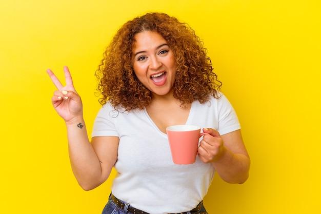 Junge lateinische kurvige frau, die eine tasse lokalisiert auf gelber wand freudig und sorglos hält, die ein friedenssymbol mit den fingern zeigt