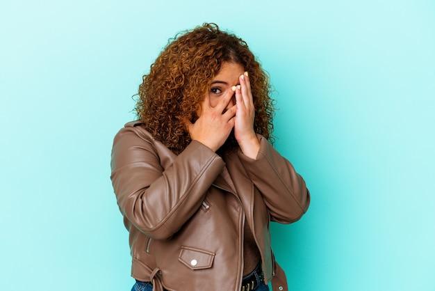 Junge lateinische kurvige frau lokalisiert auf blauem hintergrund blinzeln durch erschrockene und nervöse finger.