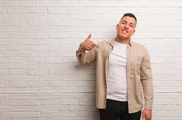 Junge lateinische mannperson, die eigenhändig auf einen hemdkopienraum, stolz und überzeugt zeigt